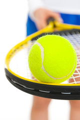 Closeup on tennis ball on racket in hand of tennis player