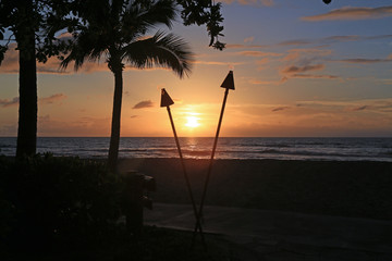 Beautiful sunset in Hawaii with tiki torches