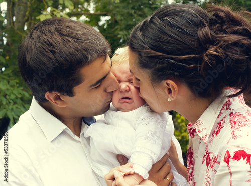 Parents kissing their crying baby