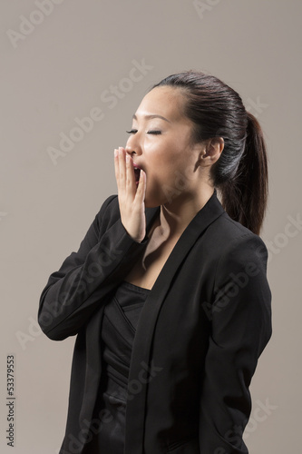 Chinese woman looking tired and Yawning