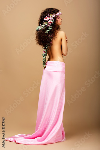 Tenderness. Gorgeous Curly Hair Brunette with Wreath of Flowers