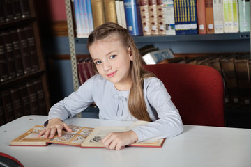 Little Girl Sitting At Table With Books