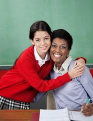 Schoolgirl Hugging Female Teacher At Desk