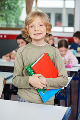Schoolboy With Books Standing At Desk