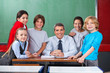 Confident Male Teacher With Schoolchildren  At Desk