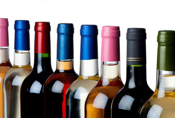 Some wine bottles in a row against white background