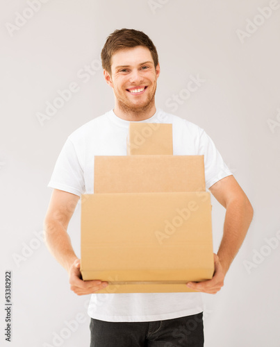 smiling man carrying carton boxes