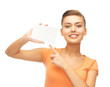 smiling woman pointing at white blank card