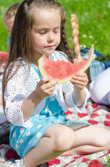 Pretty little girl eating watermelon in the park