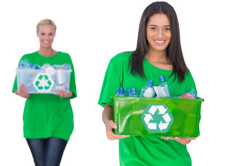 Two enivromental activists holding box of recyclables