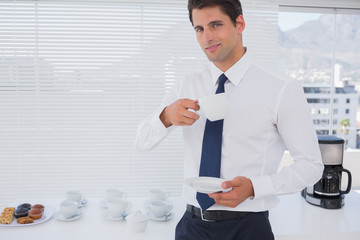 Smiling businessman having a coffee during the break