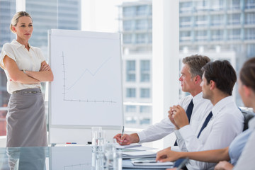 Businesswoman with arms folded in front of colleagues