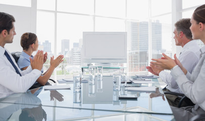 Business people applauding at a blank whiteboard