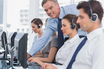 Smiling manager helping call centre employee