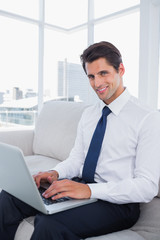 Smiling business man using laptop