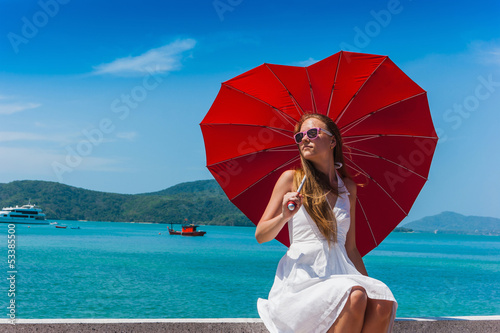 Girl with an umbrella against the sea