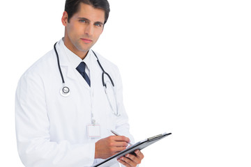 Doctor writing on his clipboard and looking at camera