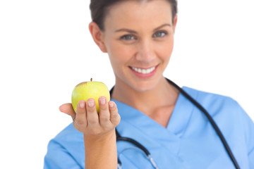 Happy surgeon holding an apple and smiling