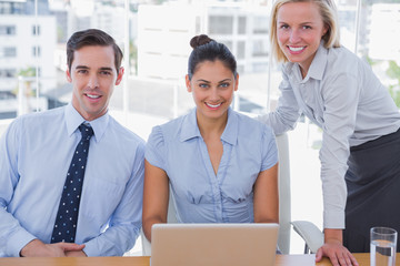 Business team with laptop smiling at camera