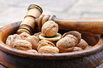 Walnuts in a wooden bowl with a Nutcracker hammer