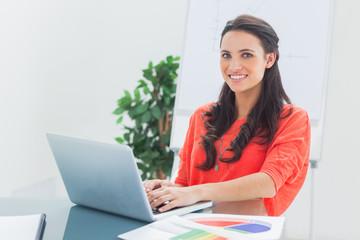 Cheerful designer working on her laptop