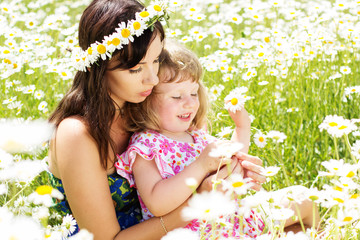 beautiful mother and little daughter in the chamomiles field