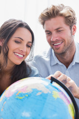 Happy couple looking at a globe