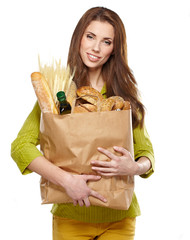 Young woman holding a grocery bag full of bread