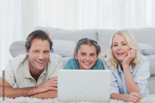 Cheerful parents and daughter using a laptop