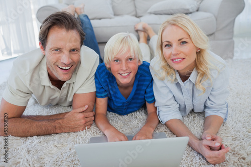 Portrait of son and parents using a laptop