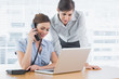 Businesswoman calling and looking at laptop with colleague