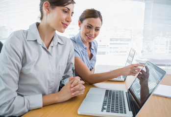 Businesswoman pointing something out on laptop for colleague