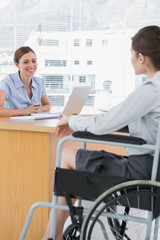 Businesswoman interviewing disabled job candidate