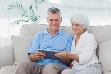 Couple using a tablet sitting on the couch
