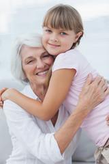 Cute girl hugging her grandmother
