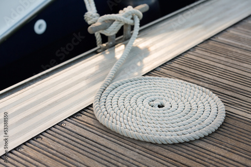 White rope coiled on a wooden dock