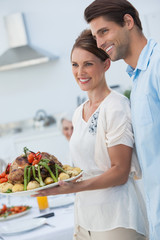 Cheerful couple showing roast chicken in the kitchen