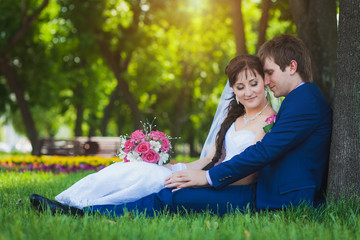 happy bride and groom are sitting on the green grass