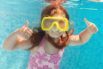 The little girl swimming underwater and smiling
