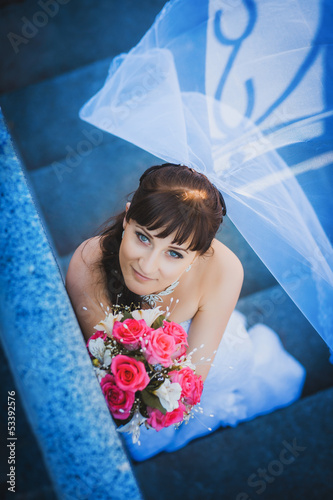 portret of happy bride in white dress on stairs