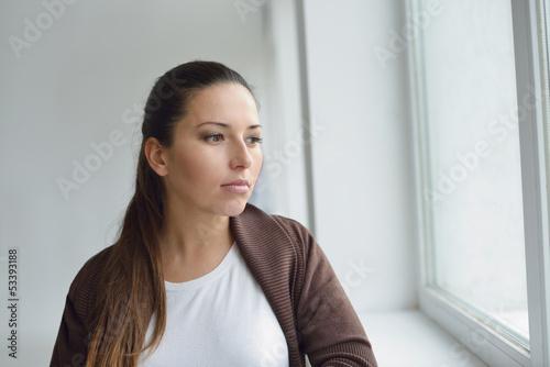 pensive woman near the window