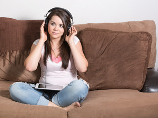 Young woman streaming music on headphones tablet
