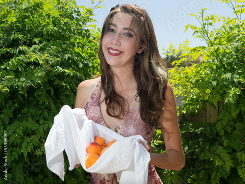 Happy young Caucasian woman holding apricots outside