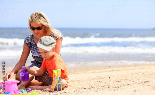Son and mother playing toys on beach