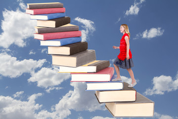 teen climbing a staircase of books