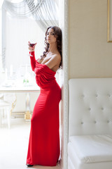 Seductive brunette posing in long red dress