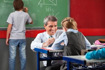 Professor Assisting Schoolgirl At Desk