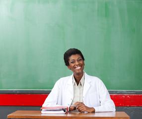Happy Female Teacher Sitting At Desk In Classroom