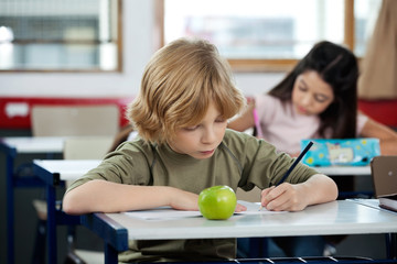 Schoolboy Writing In Book With Classmate In Background