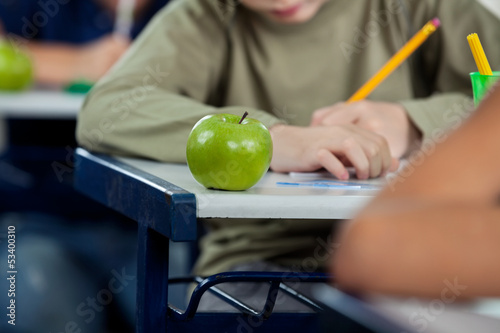 Schoolboy Writing In Book With Apple At Desk